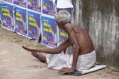 Starego człowieka żebrak czekać na datki na ulicie obok przystanku autobusowego obraz stock