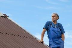 Starego człowieka działanie, budynek dach dom bez jakaś zbawczych przyrządów, jest ubranym prac ubrania, błękitny kombinezon na c Zdjęcia Stock