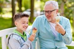 Starego człowieka i chłopiec łasowania lody przy lato parkiem Zdjęcia Royalty Free