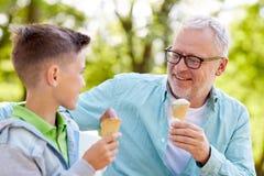 Starego człowieka i chłopiec łasowania lody przy lato parkiem Zdjęcie Royalty Free