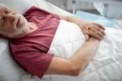 Starego człowieka lying on the beach w łóżku podczas gdy mieć śródżylnego traktowanie obraz stock