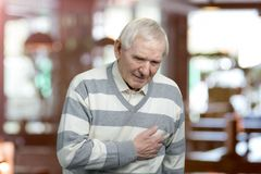 Starego człowieka mienia pierś przez kierowego infarction Zdjęcia Stock