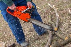 Starego człowieka mienia pomarańczowa piła łańcuchowa z jego nagimi rękami rozcięciem i gałąź umieszczająca na ziemi Pomarańczowa zdjęcia stock