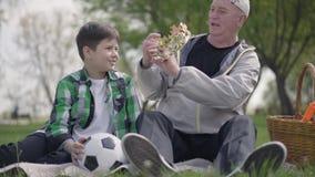 Starego cz?owieka obsiadanie z jego wnukiem na koc w parku M??czyzna bierze koron? od kosza i stawia je zdjęcie wideo