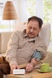 Starego człowieka pomiarowy ciśnienie krwi w domu Obrazy Stock