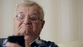 Starego człowieka wysylanie sms przez telefonu komórkowego na kanapie zdjęcie wideo