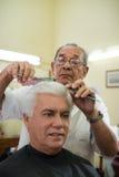 Starego fryzjer męski tnący włosy klient w fryzjer męski sklepie Fotografia Stock