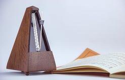 Starego rocznika drewniany metronom blisko muzycznego prześcieradła fotografia stock