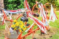 Starego stylu klasyczny bicykl z faborkiem na nim i kwiatem na koszu czerwonym i białym Zdjęcia Stock