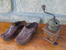 Starej antykwarskiej ręki kawowego ostrzarza i skóry chodaki na stary drewnianym Zdjęcia Royalty Free