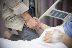Starej kobiety Chory cierpliwy lying on the beach na łóżkowym mieniu jej mąż ręka obraz royalty free