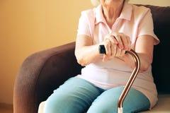 Starej kobiety obsiadanie z jego rękami na chodzącym kiju Starsi ludzie opiek zdrowotnych obrazy royalty free