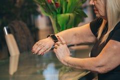 Starej kobiety use smartwatch w domu Fotografia Stock