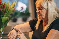 Starej kobiety use smartwatch w domu Zdjęcia Royalty Free