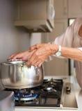 Starej kobiety wrząca woda w garnku na kuchenka wierzchołku zdjęcia royalty free