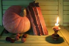 Starej książki świeczka na drewnianym stole i bania Fotografia Stock