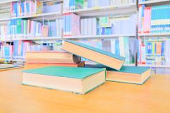 Starej książki czerwień - zieleń i rozsypisko traktat w szkolnej bibliotece na drewnianym stole rozmyty półka na książki tło obraz stock