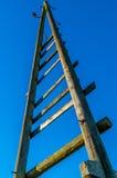Starej trójbok elektryczności drewniany słup z niebieskim niebem Zdjęcia Royalty Free