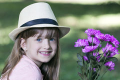She stares at the camera, laughing and holding a bouquet of flow. Little cute smiling girl with hat looking at the camera and holding a bouquet of flowers Royalty Free Stock Images
