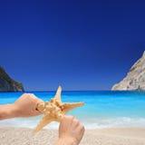 starfish персоны удерживания пляжа песочные стоковые изображения