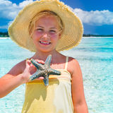 Starfish. Child  with straw hat holding a starfish Royalty Free Stock Photo