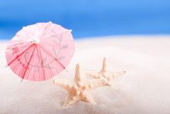 Starfish auf dem Strand unter einem Regenschirm Stockfoto