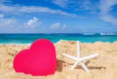 Starfish with big heart on the sandy beach Stock Photo
