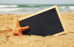 Starfish and chalkboard, on sea sand and ocean horizon Stock Photography