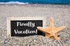 Starfish and chalkboard with the text finally vacation. Closeup of a starfish and a wooden-framed chalkboard with the text finally vacation written in it, placed Stock Photos
