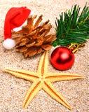 Starfish, christmas ball, christmas hat and pine twig on  sand Royalty Free Stock Image