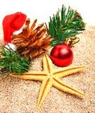 Starfish, christmas ball, christmas hat and pine twig on the sand Stock Photo