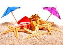 Starfish, christmas ball, gift box on the sand Stock Photography