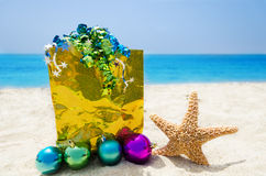Starfish with Christmas balls and gift on the beach - holiday co Stock Images
