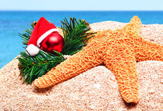 Starfish, christmas baubles and pine twig on the sand Stock Images