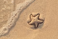 Starfish drawn on the beach sand being washed away by a wave. Foaming sea wave coming to wash a picture on wet yellow stock photography