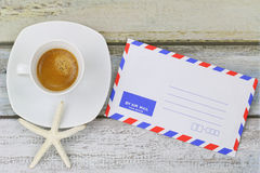 Starfish on Espresso coffee next to blank classic air mail envel Royalty Free Stock Photography