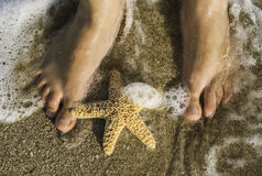 Starfish and feet on the beach Royalty Free Stock Photos
