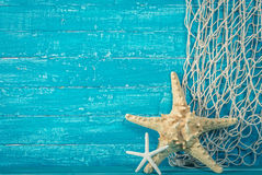 Starfish and fishing net on blue royalty free stock photo