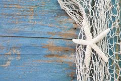 Starfish in a fishing net with a blue background Royalty Free Stock Photo