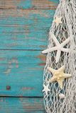 Starfish in a fishing net with a turquoise wooden background, po. Starfish in a fishing net with a turquoise wooden background. Postcard royalty free stock images
