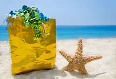 Starfish with gift bag on the beach - holiday concept Royalty Free Stock Photos