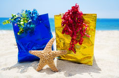 Starfish with gift bags on the beach - holiday concept Stock Photo