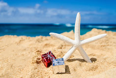 Starfish with gift boxes on the sandy beach Royalty Free Stock Images