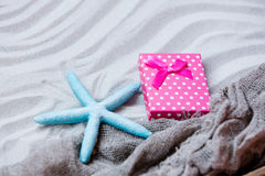 Starfish, gift and fishnet on the sand Stock Photo