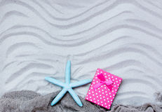 Starfish, gift and fishnet on the sand Stock Photography