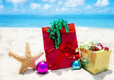 Starfish with gifts and christmas balls on the beach Royalty Free Stock Photo