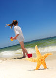 Starfish and girl on beach Royalty Free Stock Image