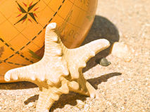 Starfish and the globe Stock Photography