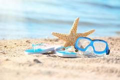 Starfish, goggles and flip flops on sand near se royalty free stock image