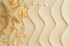 Starfish on golden beach sand with wavy lines. Scattered dried starfish in different sizes arranged to the left side on golden beach sand with decorative wavy Royalty Free Stock Photo